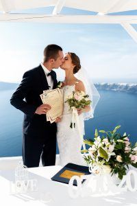 Groom and bride with wedding certificates at aisle tent sea background