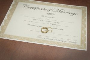 gold wedding rings with a marriage certificate